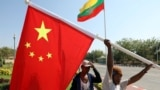 FILE - Workers put up flags a day before Chinese President Xi Jinping's visit to Myanmar in Naypyitaw, Myanmar, January 16, 2020.