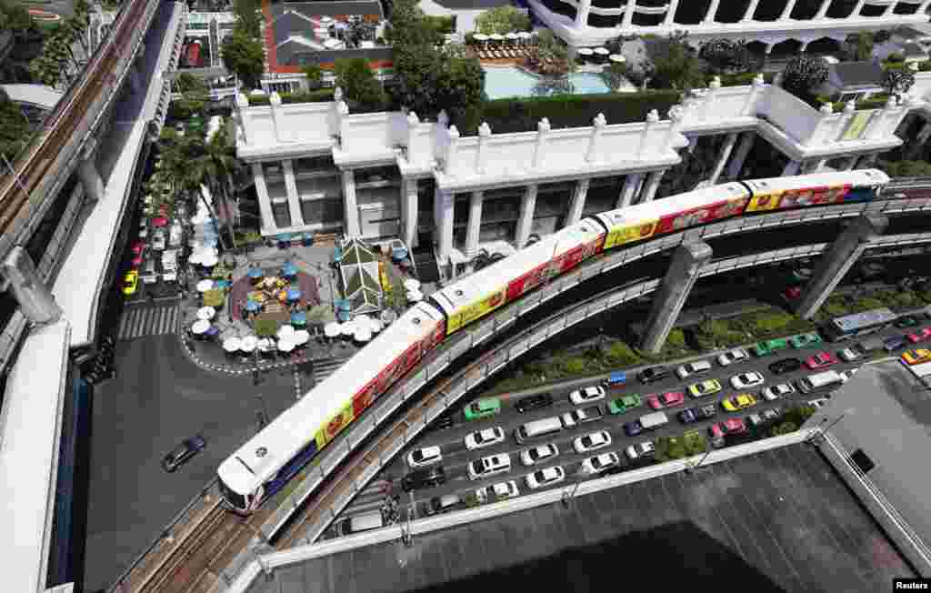 A skytrain passes over vehicles on the road in Bangkok, Thailand..