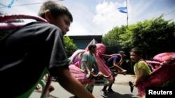 Niños nicaraguenses disfrazados juegan en la calle antes de las festividades en honor del santo patrón de la nación Santo Domingo de Guzmán. Managua, 1 de agosto de 2018.