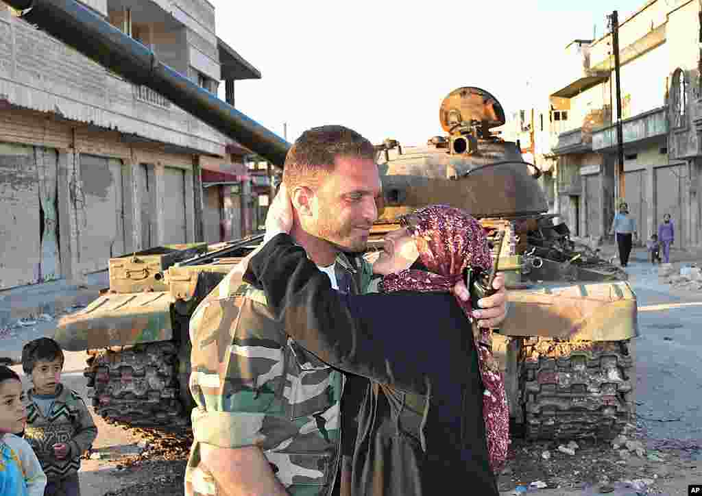 A Syrian woman kisses a soldier from the Free Syrian Army in front a destroyed Syrian army forces tank that was attacked during clashes between the Syrian government forces and the Syrian rebels, in Rastan, Homs, March 21, 2012. (AP)