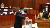 In this photo released by Cambodia's National Assembly, Cambodian Prime Minister Hun Sen drops a ballot into a box in the National Assembly hall in Phnom Penh, Cambodia, Monday, Oct. 25, 2021. (Cambodia's National Assembly via AP)
