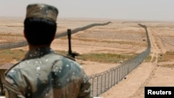 FILE - A member of the Saudi border guards force watches Saudi Arabia's northern borderline July 14, 2014.