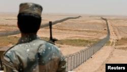 Seorang tentara penjaga perbatasan Saudi mengawasi tembok perbatasan di Saudi utara, dekat perbatasan Irak (foto: dok).