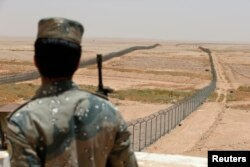 A member of the Saudi border guards force stands guard next to a fence on Saudi Arabia's northern borderline with Iraq July 14, 2014.