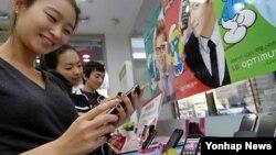 한국 서울에서 전시된 스마트폰을 만져보는 소비자들. (자료사진)