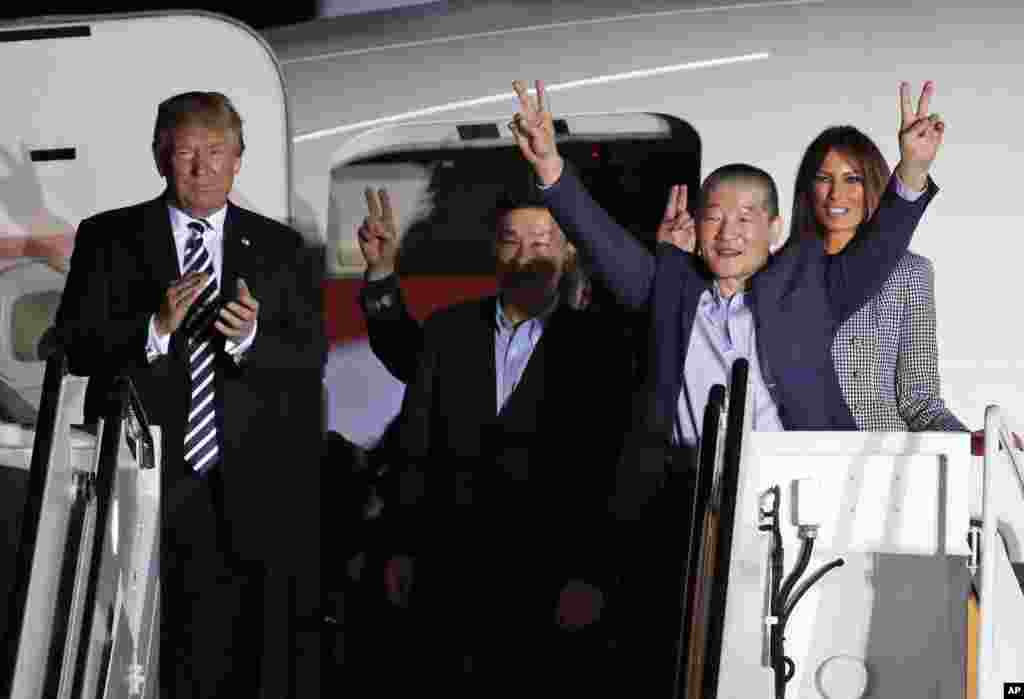President Donald Trump and first lady Melania Trump greet former North Korean detainees Kim Dong Chul, second right, Tony Kim, center, and Kim Hak Song, behind Tony Kim, upon their arrival at Joint Base Andrews, Maryland.