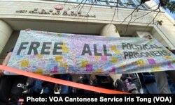 在西九法院大楼外排队的市民拉起用英文写上释放所有政治犯的大型横额 (美国之音/汤惠芸)