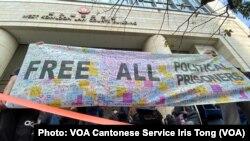 在西九法院大樓外排隊的市民拉起用英文寫上釋放所有政治犯的大型橫額 (攝影:美國之音湯惠芸)