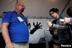 A journalist takes notes while talking with Johnny Matheny (L), from the Johns Hopkins University Applied Physics Lab, as he shows his prosthetic hand during the DARPA (Defense Advanced Research Projects Agency) Demo Day exhibition at the Pentagon.