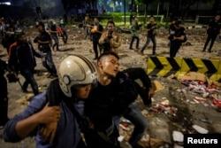 Seorang polisi membawa rekannya yang terluka dalam aksi unjuk rasa 23 Mei 2019 di Jakarta (Foto: Antara).
