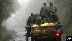 Congolese M23 rebels carry goods in the back of a truck near the Congo-Uganda border town of Bunagana, DRC. (file)