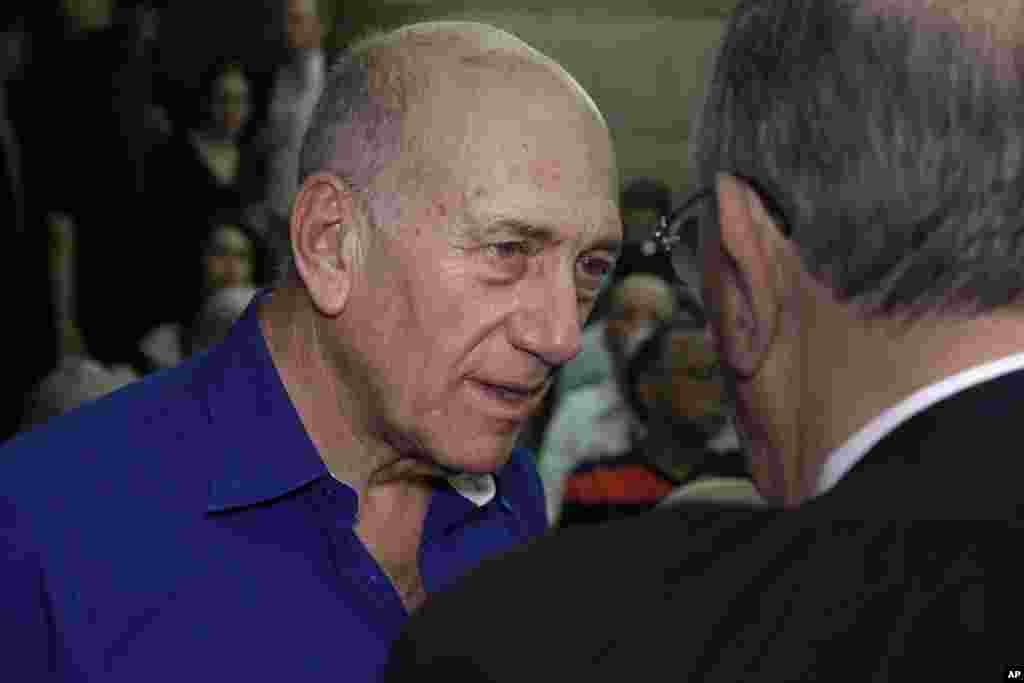 Israel's former prime Minister Ehud Olmert speaks to a lawyer upon his arrival at the Tel Aviv District Court in Israel, May 13, 2014.