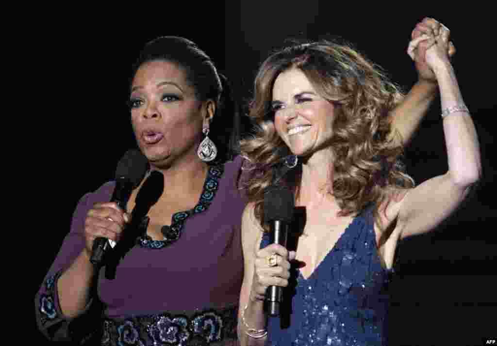 Опра Уинфри и Мария Шрайвер держаться за руки во время ток-шоу «Oprah's Surprise Spectacular» в Чикаго, 17 мая 2011г.