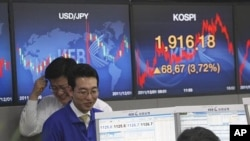 Currency traders react in front screens at the Korea Exchange Bank headquarters in Seoul, South Korea, December 1, 2011.