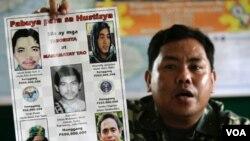 Dalam foto dari tahun 2006 ini, Pejabat militer Filipina Mayor Mabini Abduhadi menunjukkan poster bergambar tokoh Al-Qaida yang diduga terkait dengan gerakan MILF, termasuk Umar Patek (kiri bawah).