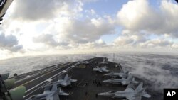 Fog rises over the Atlantic Ocean as the aircraft carrier USS Dwight D. Eisenhower conducts flight operations, 4 Jan 2010