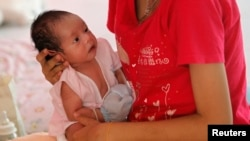 FILE - An unnamed teenager holds her son at the Association for the Promotion of the Status of Women in Bangkok.
