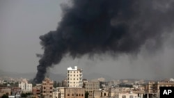 Smoke rises after Saudi-led airstrikes hit a food factory in Sanaa, Yemen, Aug. 9, 2016. In the air campaign by Saudi Arabia and its allies against Yemen's Shiite rebels, rights experts say the Saudi-led coalition is failing to distinguish between civilia