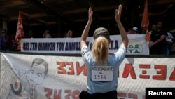 Seorang polisi kota Athena memberikan tepuk tangan kepada demonstran yang melakukan protes atas PHK di sektor pemerintahan (12/7).