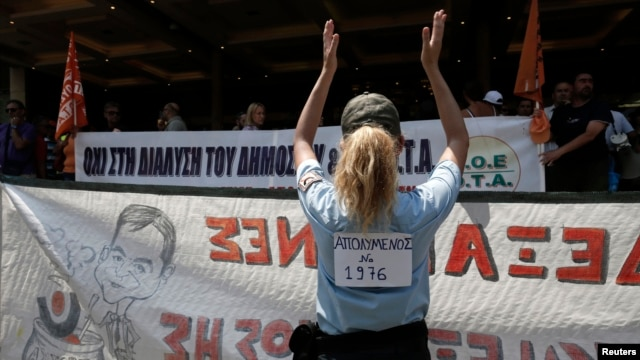 A municipal police officer applauds during a rally against public sector layoffs, which the government has promised its international lenders in exchange for bailout funds, Athens, Greece, July 12, 2013.