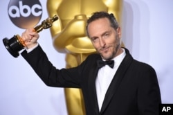 "Emmanuel Lubezki poses with the award for best cinematography for ""The Revenant"" in the press room at the Oscars on Feb. 28, 2016, at the Dolby Theatre in Los Angeles."