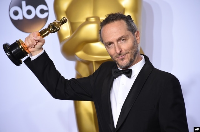 """Emmanuel Lubezki poses with the award for best cinematography for """"The Revenant"""" in the press room at the Oscars on Feb. 28, 2016, at the Dolby Theatre in Los Angeles."""