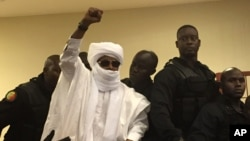 Chad's former dictator Hissene Habre raises his hand during court proceedings in Dakar, Senegal, May 30, 2016.