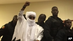 FILE - Chad's former dictator Hissene Habre raises his hand during court proceedings in Dakar, Senegal, May 30, 2016.