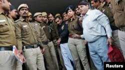 Cảnh sát áp tải tài xế taxi Uber Shiv Kumar Yadav ra tòa ở New Delhi.