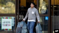 A man carries bags out of a department store in Alameda, California, Dec. 17, 2015. U.S. consumer spending rebounded in November after a weak showing in October while a key inflation gauge posted the fastest year-over-year increase in 11 months.