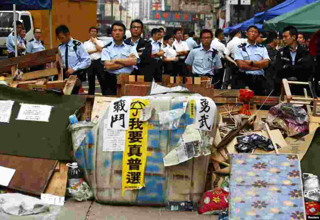 Policemen stand guard behind a barricade set up by pro-democracy demonstrators, to be removed by bailiffs under a court injunction, at Mong Kok shopping district in Hong Kong, Nov. 19, 2014.