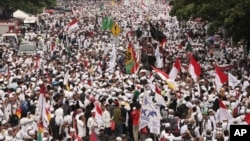 Muslim protesters march during a demonstration in Jakarta, Indonesia, Nov. 4, 2016. Tens of thousands of hard-line Muslims converged Friday on the center of the Indonesian capital to demand the arrest of its minority-Christian governor for alleged blasphemy.