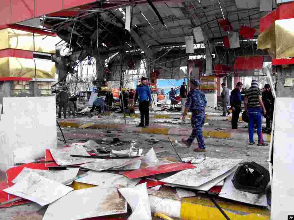 شهروندان غيرنظامی و نيروهای انتظامی محل انفجار در حله (۹۰کيلومتری جنوب بغداد) را بررسی می کنند. - ۱۸ اسفندماه
