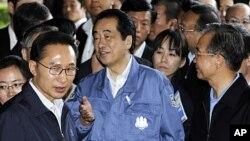 日本首相菅直人(中)与韩国总统李明博(左)和中国总理温家宝(右)周六参观福岛疏散中心