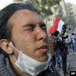 An injured protester receives treatment during clashes with riot police along a road leading to the Interior Ministry, near Tahrir Square in Cairo, November 23, 2011