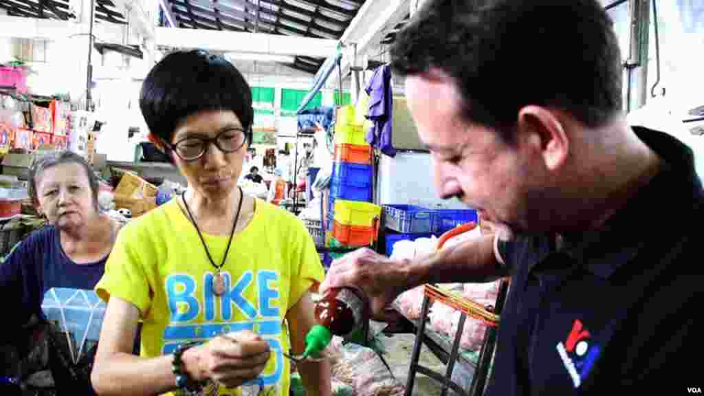 VOA Correspondent Steve Herman pours Sriracha hot sauce onto a spoon for Aree Khajonrungruang to try in the Si Racha central food market. (Z. Aung/VOA)