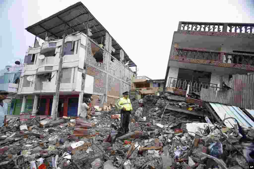 A police officer stands on debris, next to buildings destroyed by an earthquake in Pedernales, Ecuador, April 17, 2016. The earthquake flattened buildings and buckled highways along its Pacific coast, sending the Andean nation into a state of emergency.