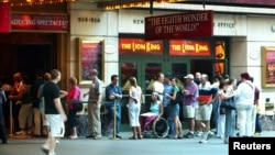"""FILE - People wait for tickets outside of the Broadway musical """"The Lion King,"""" in New York City."""