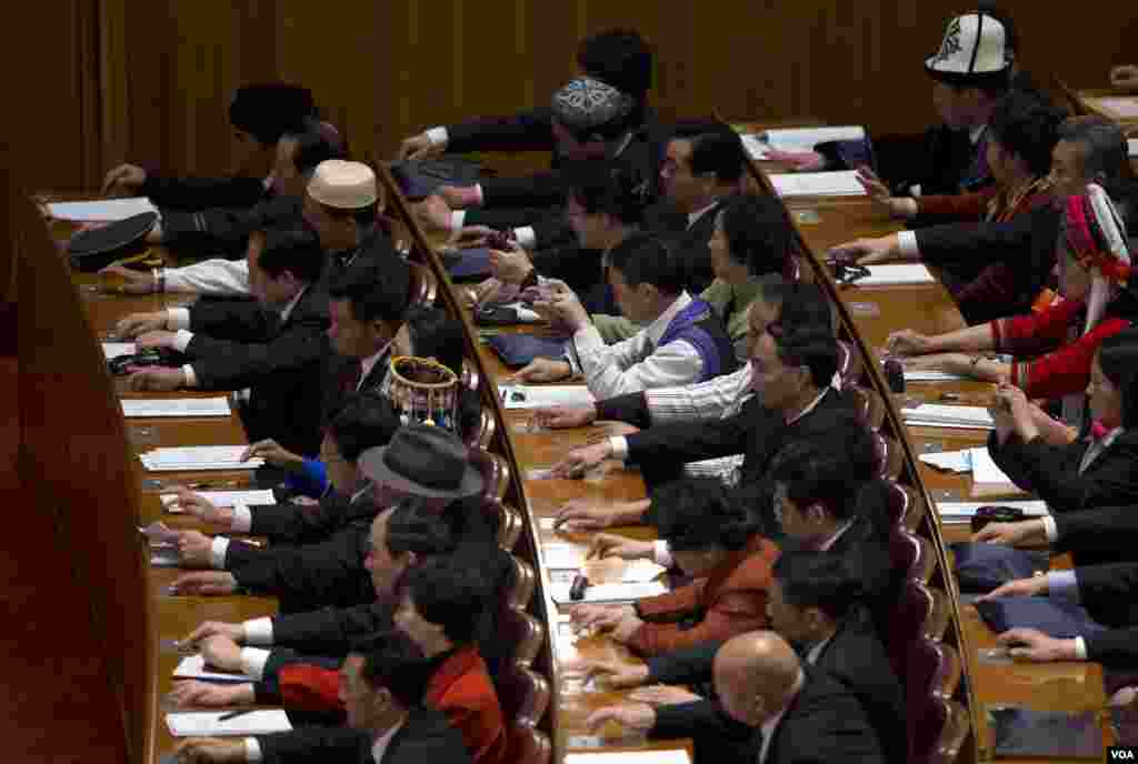 Delegates press buttons to cast their approval for draft proposals during the opening session of the annual National People's Congress in Beijing's Great Hall of the People, March 5, 2013.