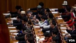 2013年3月5日在人民大会堂召开的第十二届人大开幕式上按钮批准建议草案。(美国之音东方拍摄)