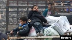 Anak-anak laki-laki duduk di atas tumpukan barang, menunggu evakuasi dari daerah pemberontak di Aleppo timur, Suriah (16/12).