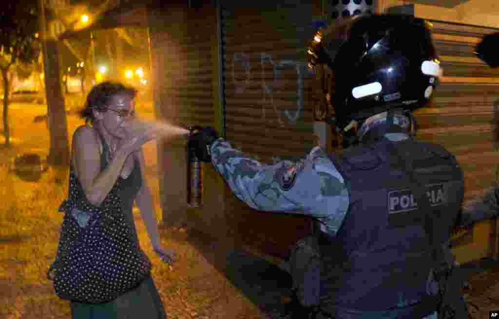 Seorang polisi militer menggunakan semprotan merica ke arah seorang pengunjuk rasa selama demonstrasi soal kondisi ekonomi di Rio de Janeiro, Brazil.
