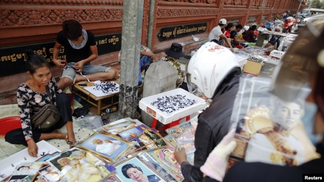Vendors sell pictures of the royal family, as the country prepares for the funeral of Cambodia's late King Norodom Sihanouk, near the Royal Palace in Phnom Penh, January 31, 2013.