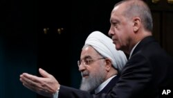 FILE - Turkey Iran SyriaTurkey's President Recep Tayyip Erdogan, right, gestures to Iran's President Hassan Rouhani, as they arrive for a news conference following their meeting at the Presidential Palace in Ankara, Dec. 20, 2018.