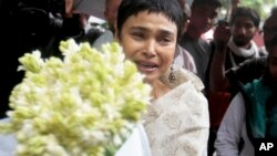 An unidentified woman brings flowers to pay respect to the people who died at Holey Artisan Bakery in Dhaka.