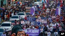 Sebuah boneka yang menggambarkan sosok Presiden Rodrigo Duterte memimpin para pemrotes berbaris menuju Istana Kepresidenan di Manila, Filipina, menandai perayaan Hari Perempuan Internasional, 8 Maret 2018.