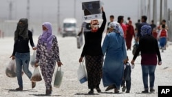 Syrian refugees walk at a refugee camp in Suruc, on the Turkey-Syria border, Friday, June 19, 2015. (AP Photo/Emrah Gurel)