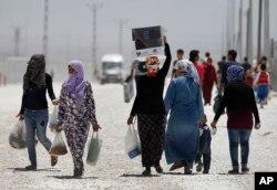 Người tị nạn Syria đi bộ tại một trại tị nạn ở Suruç, trên biên giới Thổ Nhĩ Kỳ-Syria.