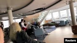 Para penumpang melindungi diri dari atap yang roboh di kapal pesiar Viking Sky saat kapal itu mengalami kerusakan mesin di dekat Hustadvika, Norwegia, 23 Maret 2019, in this still image obtained from a social media video.