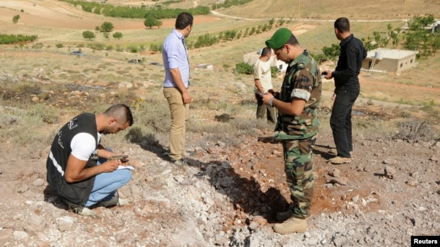 Lebanese soldiers inspect a site which was hit by a rocket, which residents say was fired from Syria overnight, in the town of Seriine in the Bekaa valley, Lebanon, Jun. 1, 2013.